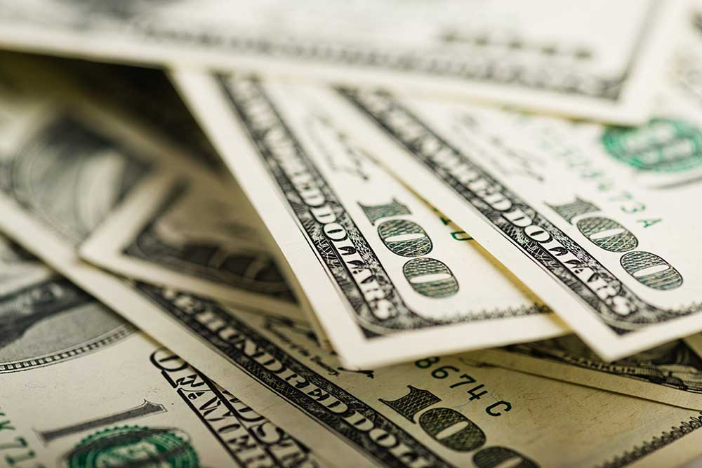 Stack of money used to buy an recreation vehicle after thorough RV inspection services are preformed